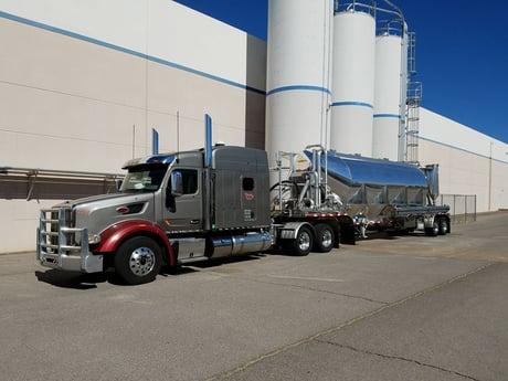 dry-bulk-truck-next-to-silos-small